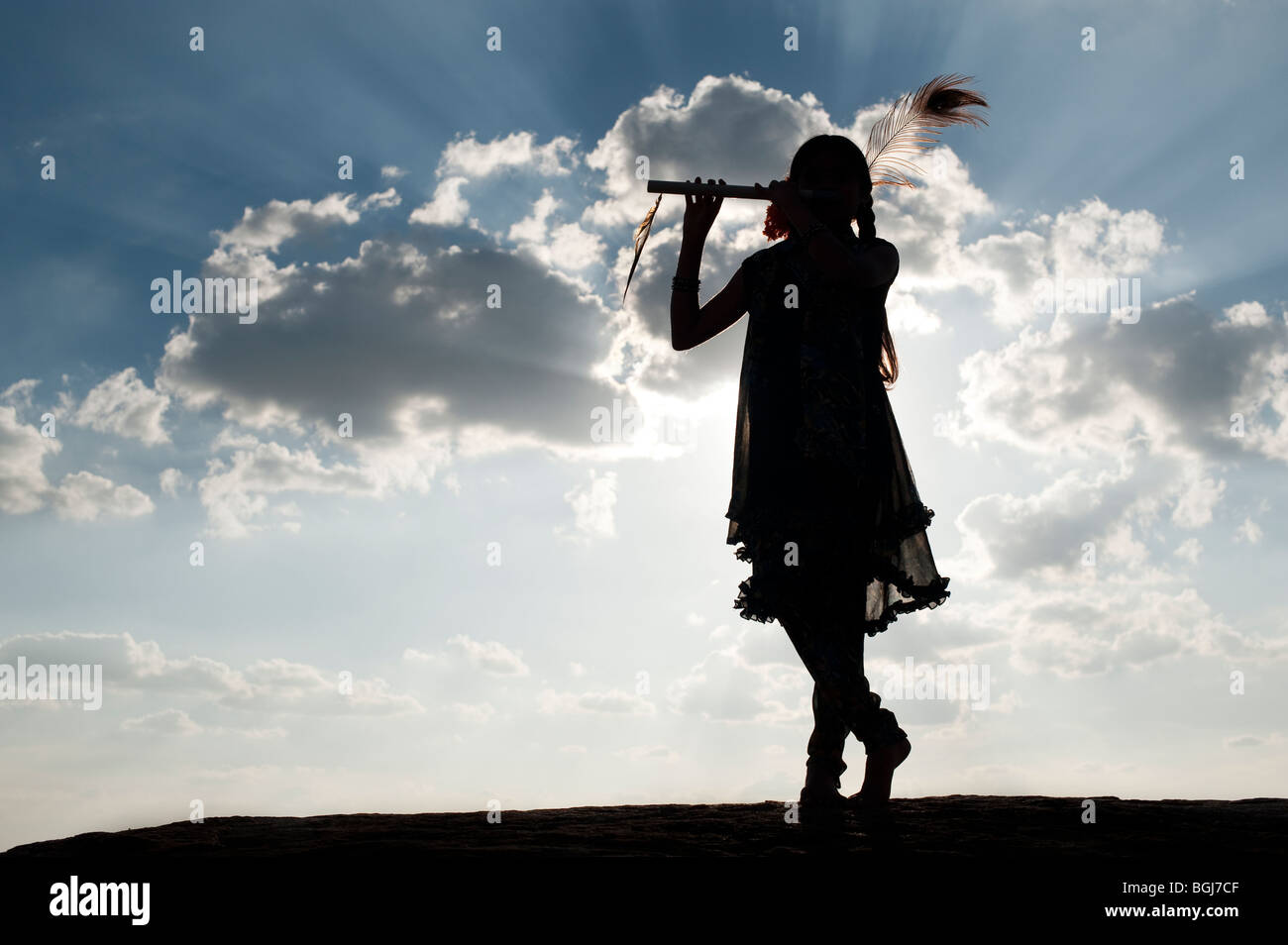 Indian girl in krishna silhouette pose at sunset in the indian countryside - Stock Image