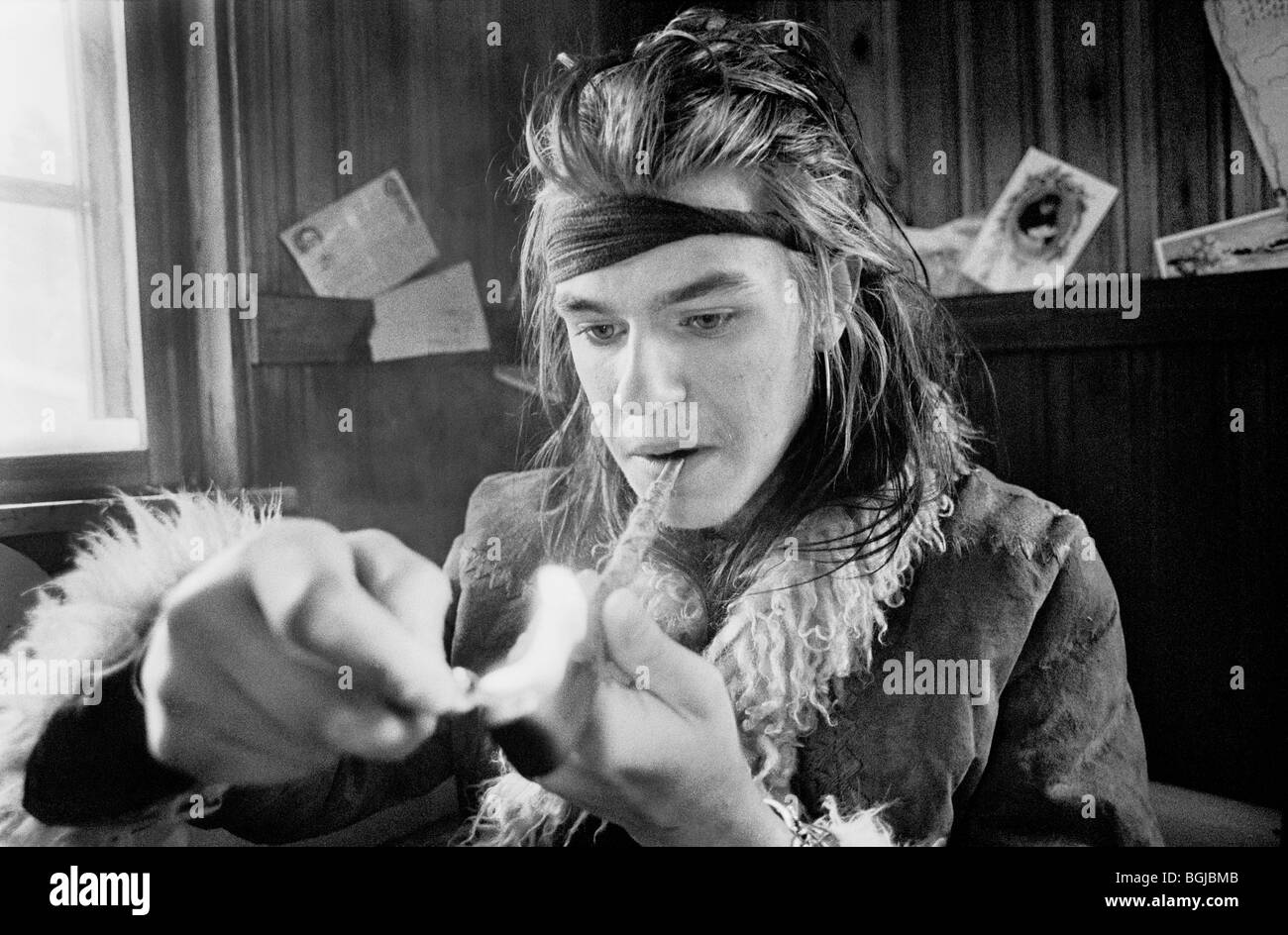 Young man lighting a pipe at alternative lifestyle commune in Skogsnäs, Northern Sweden. - Stock Image
