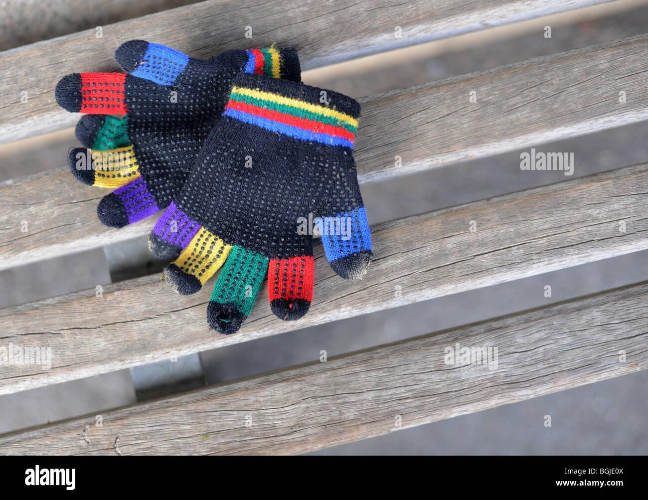 children rainbow gloves on bench - Stock Image