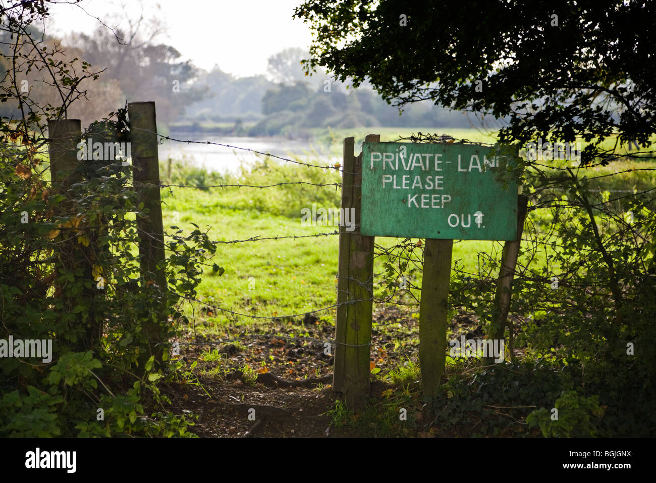 Fence and notice marking a boundary. Sign reads 'Private Land Please Keep Out'. Borders of Hampshire and - Stock Image