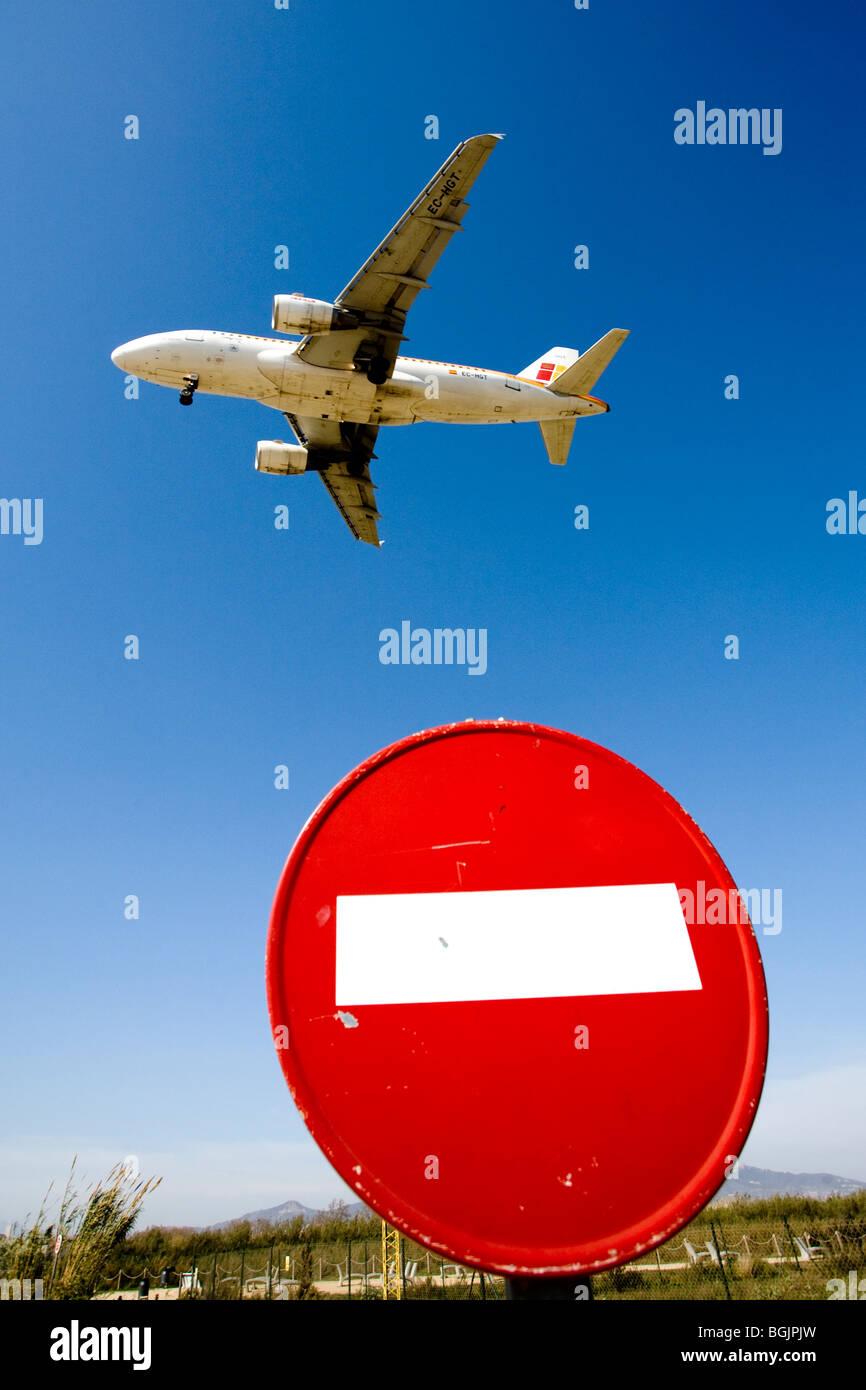 plane landing and wrong way traffic sign - Stock Image