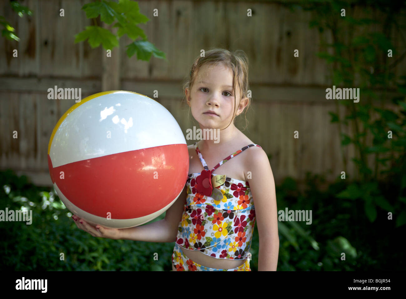 a bored young girl holding beach ball wearing a bathing suit in summer - Stock Image