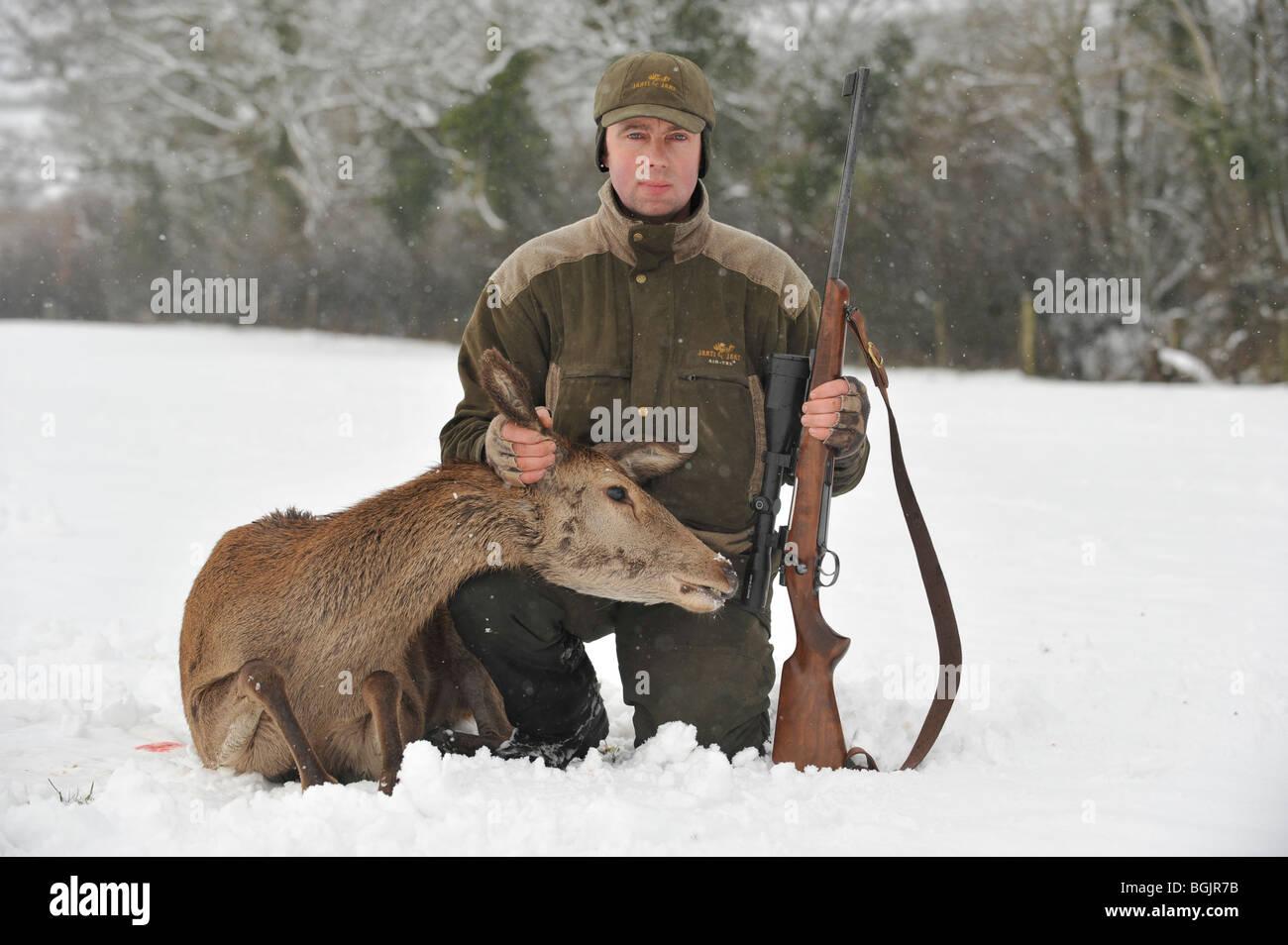 deer stalker with his shot red deer - Stock Image