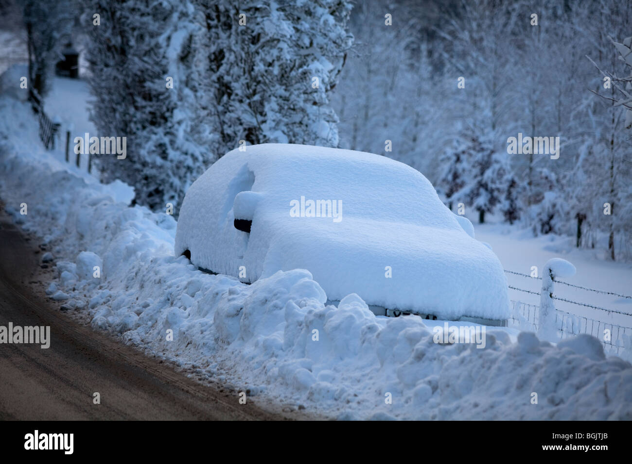 A car stranded in snow by the side of a road in Broadway, Worcestershire, UK - Stock Image