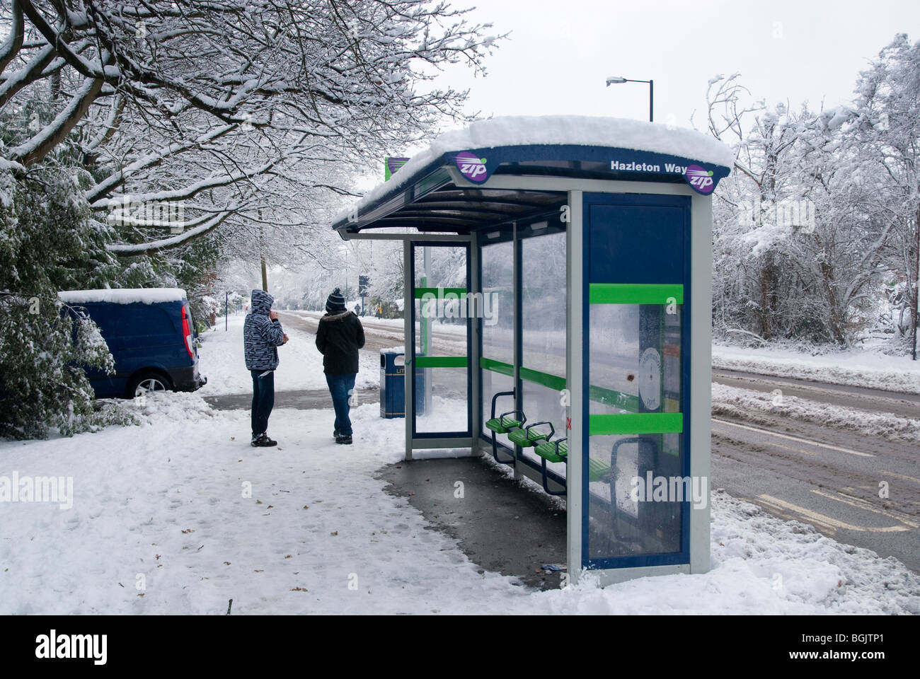 two people waiting at snow covered bus stop when no buses running. Major snow fall A3 area of hampshire january - Stock Image