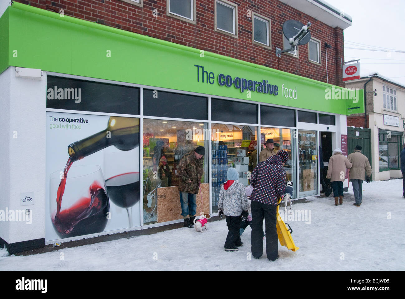 people entering open Co op for supplies on snowy day. Major snow fall A3 area of hampshire january 2010 - Stock Image