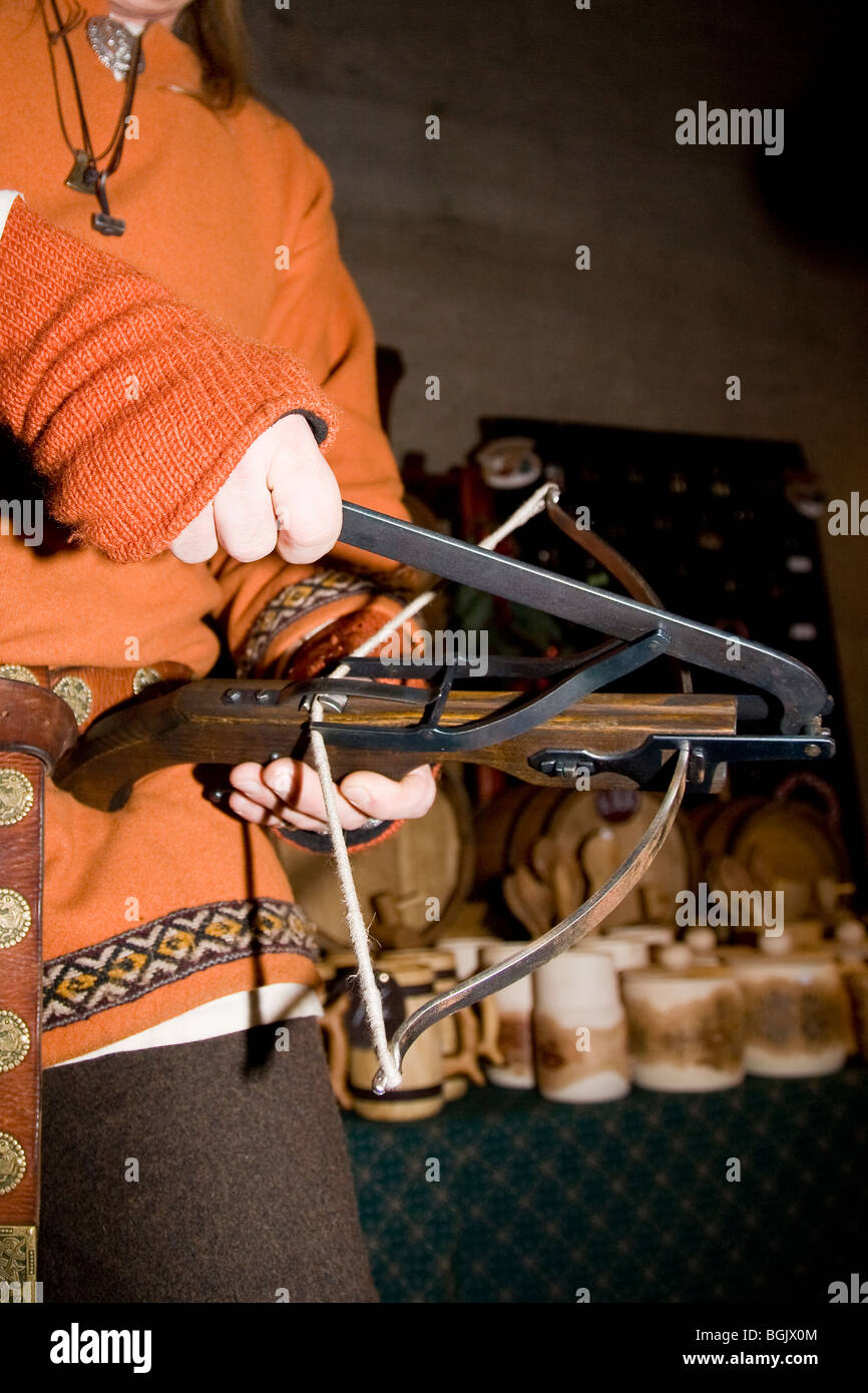 Viking stall holder demonstrates a one-handed crossbow - Stock Image