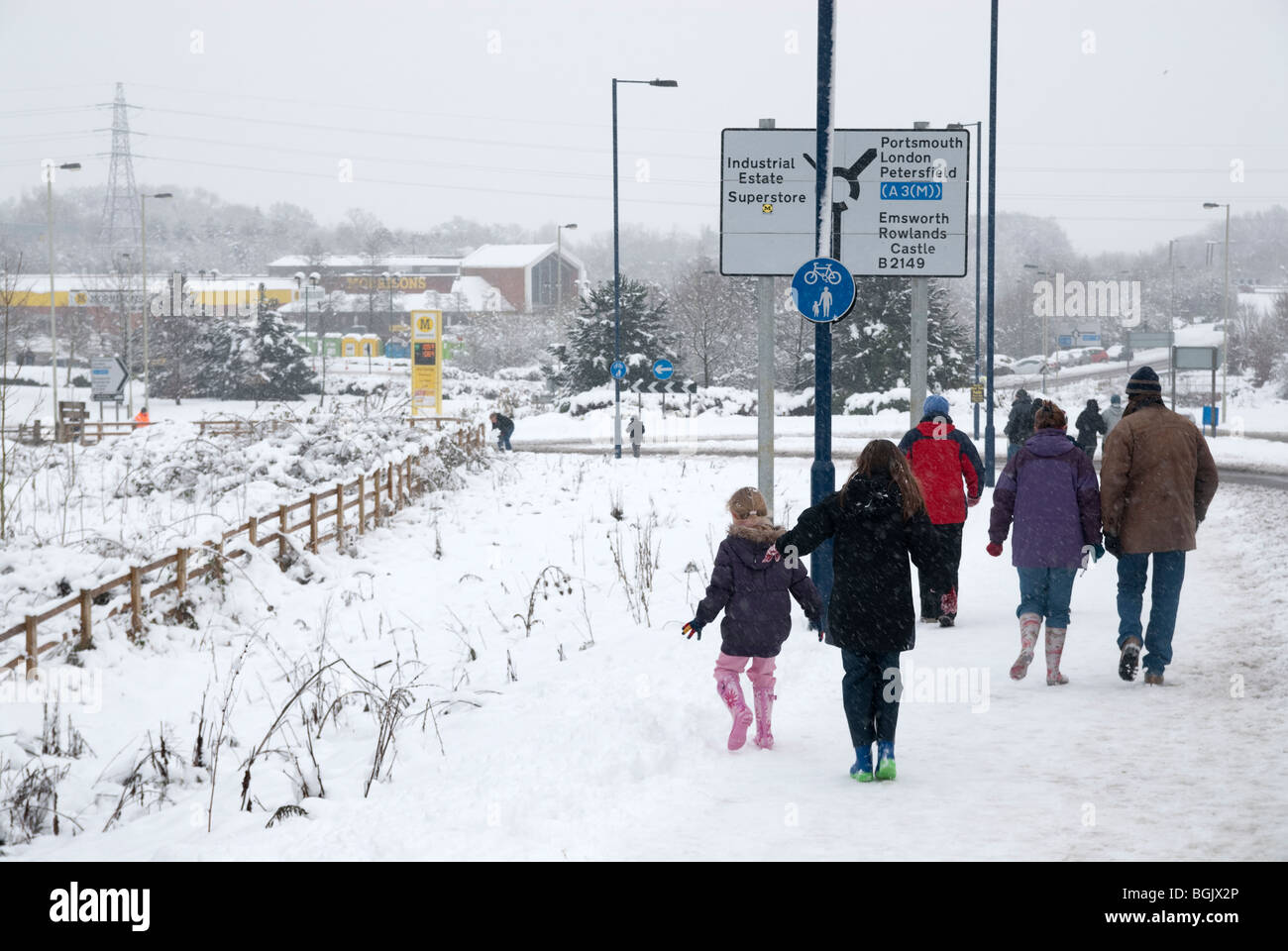 Familys walking to morrison supermarket for food during transport chaos caused by Major snow fall A3 area of hampshire - Stock Image