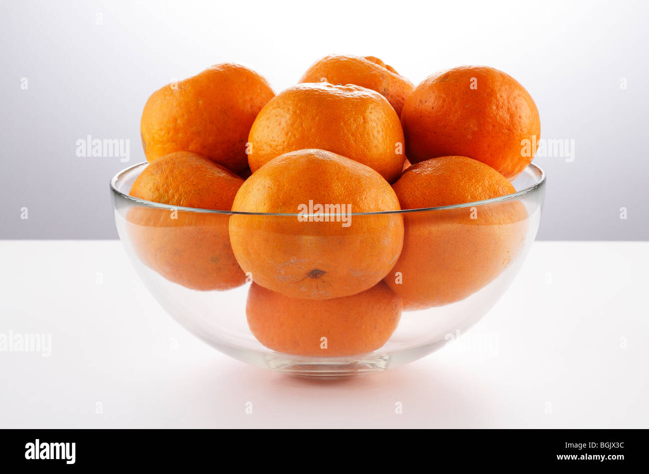 Mandarin oranges in a glass bowl on a white table with a gradient background - Stock Image