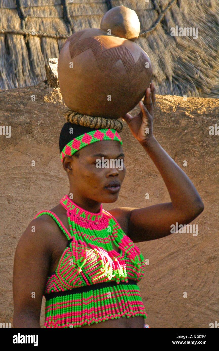 Zulu woman carrying clay pot on head, Shakaland, South ...