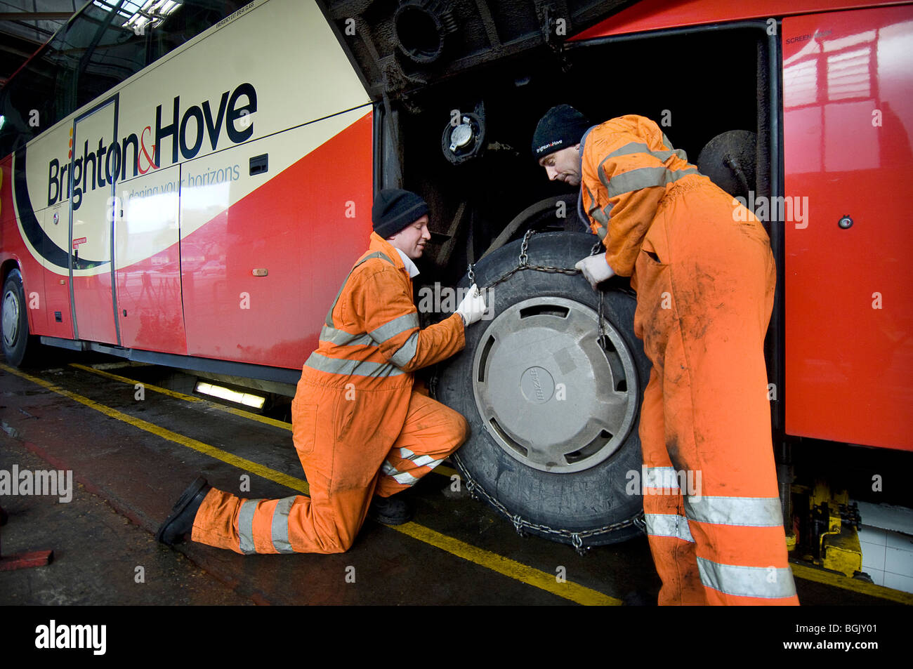 Two mechanics fitting snow chains to a bus wheel using a bus garage inspection pit. - Stock Image