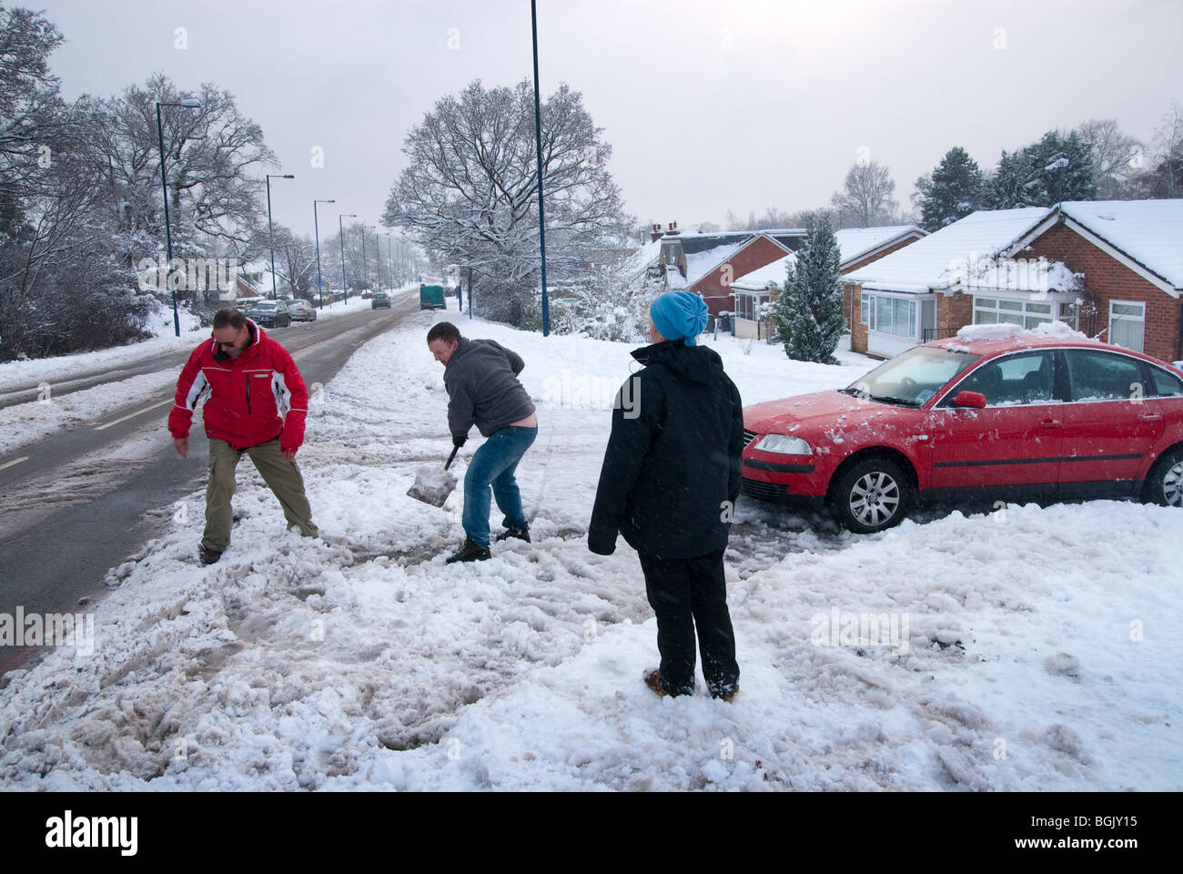 clearing snow to get stuck car to cleared main road. Major snow fall A3 area of hampshire january 2010 - Stock Image