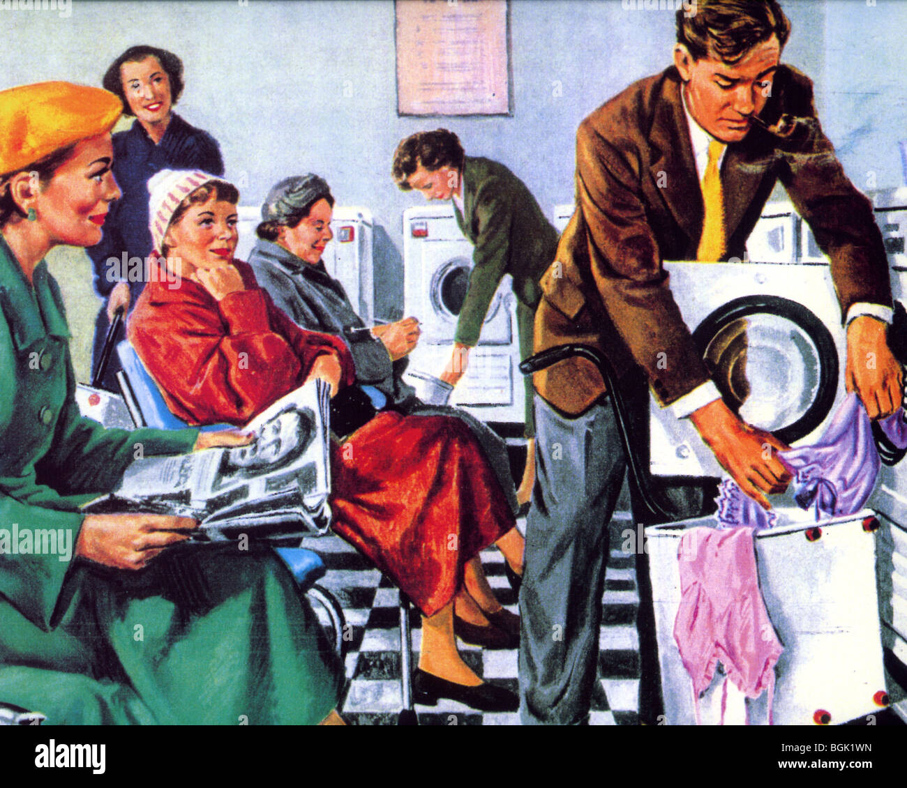 FIFTIES LAUNDERETTE  - pipe smoking husdband struggles with the new-fangled machine - Stock Image