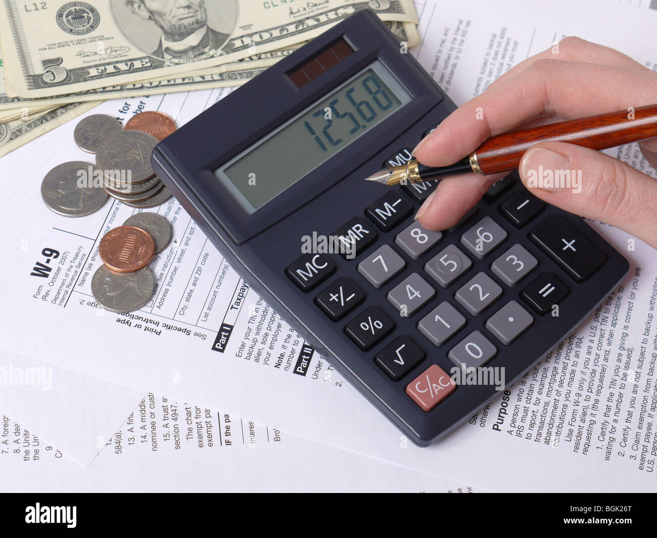 Female hand calculating taxes on calculator with W-9 income tax forms underneath - Stock Image