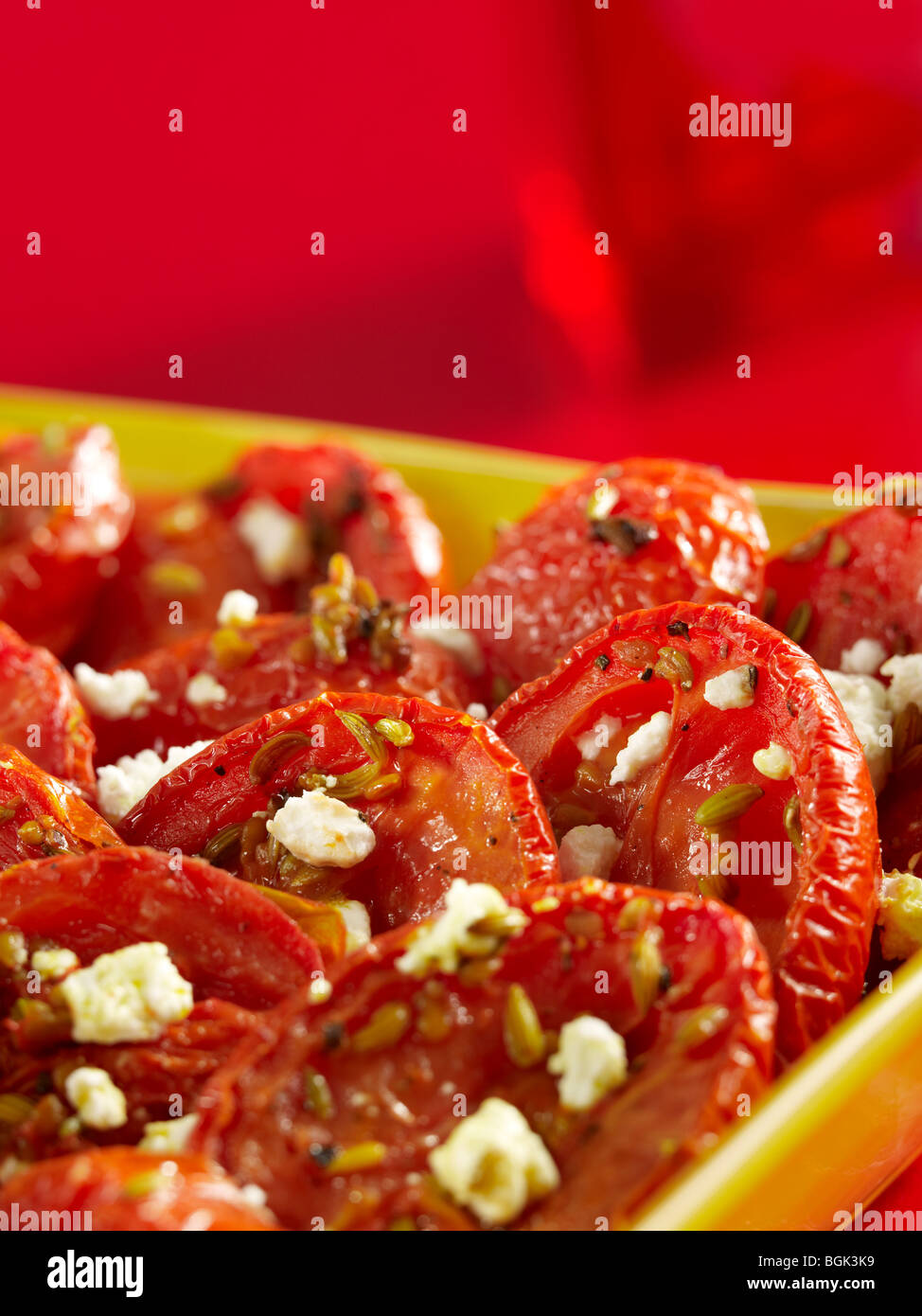 Roasted tomatoes with feta cheese in casserole dish - Stock Image
