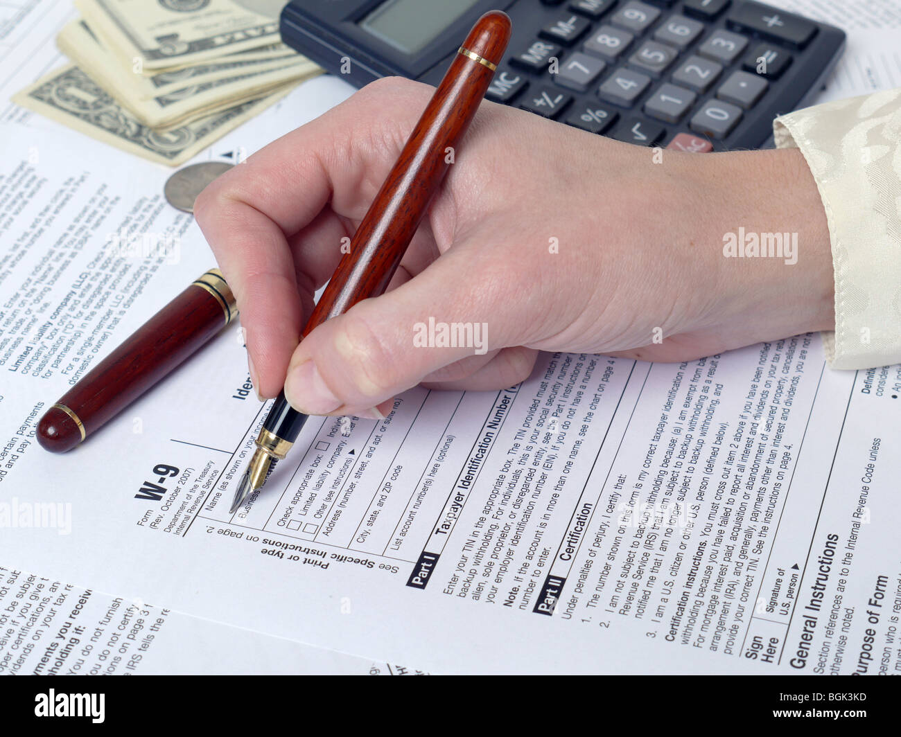 Female hand filling out W-9 income tax form with pen - Stock Image