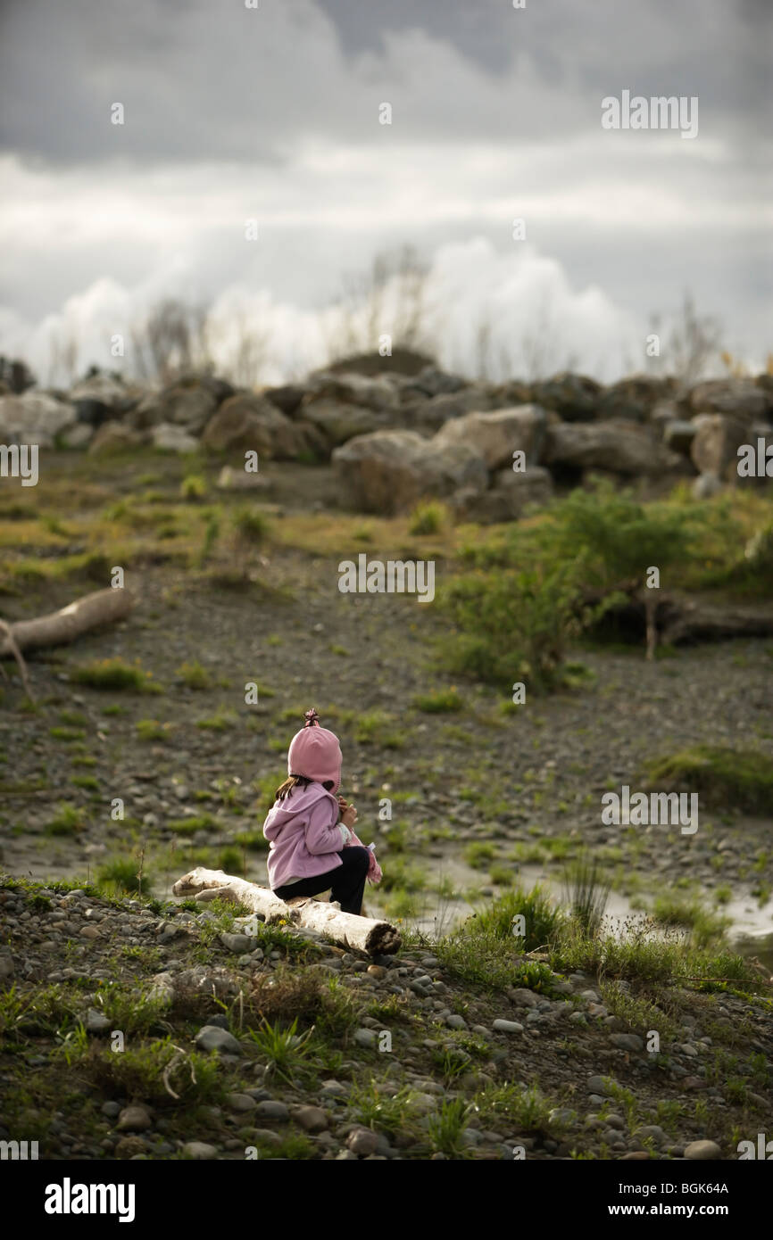 Girl aged five sits close to riverbank, piled rocks on horizon part of flood defense - Stock Image