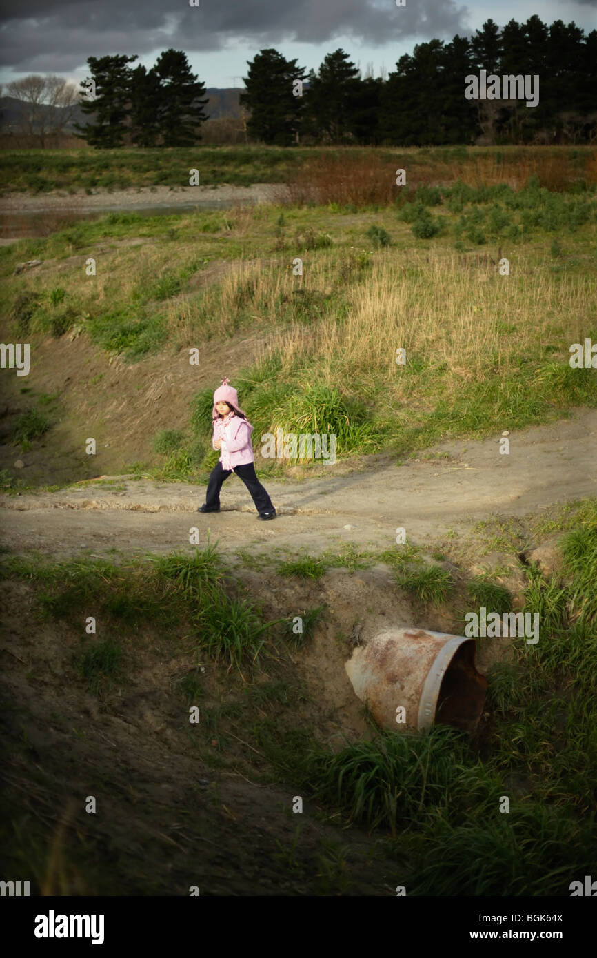 Girl aged five crosses drainage ditch - Stock Image