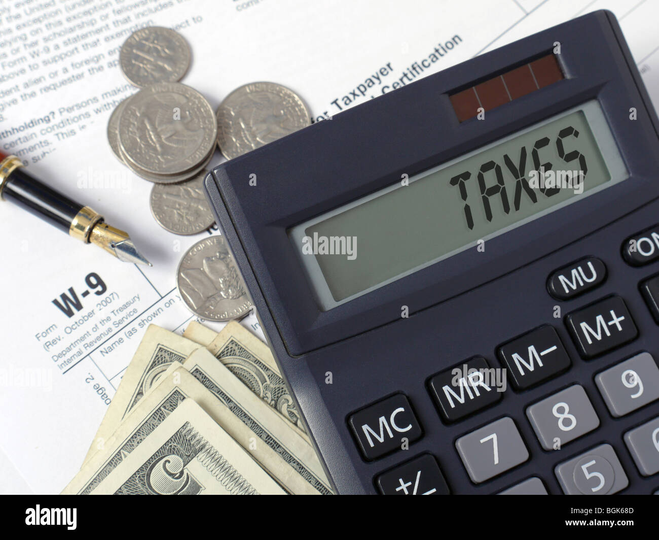Calculator with lcd displaying Taxes word placed on W-9 income tax forms with pen, and american dollars - Stock Image