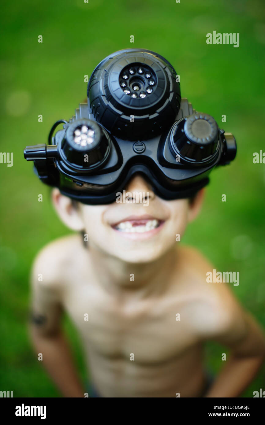 Night Sight, boy wears plastic toy functioning night vision goggles - Stock Image