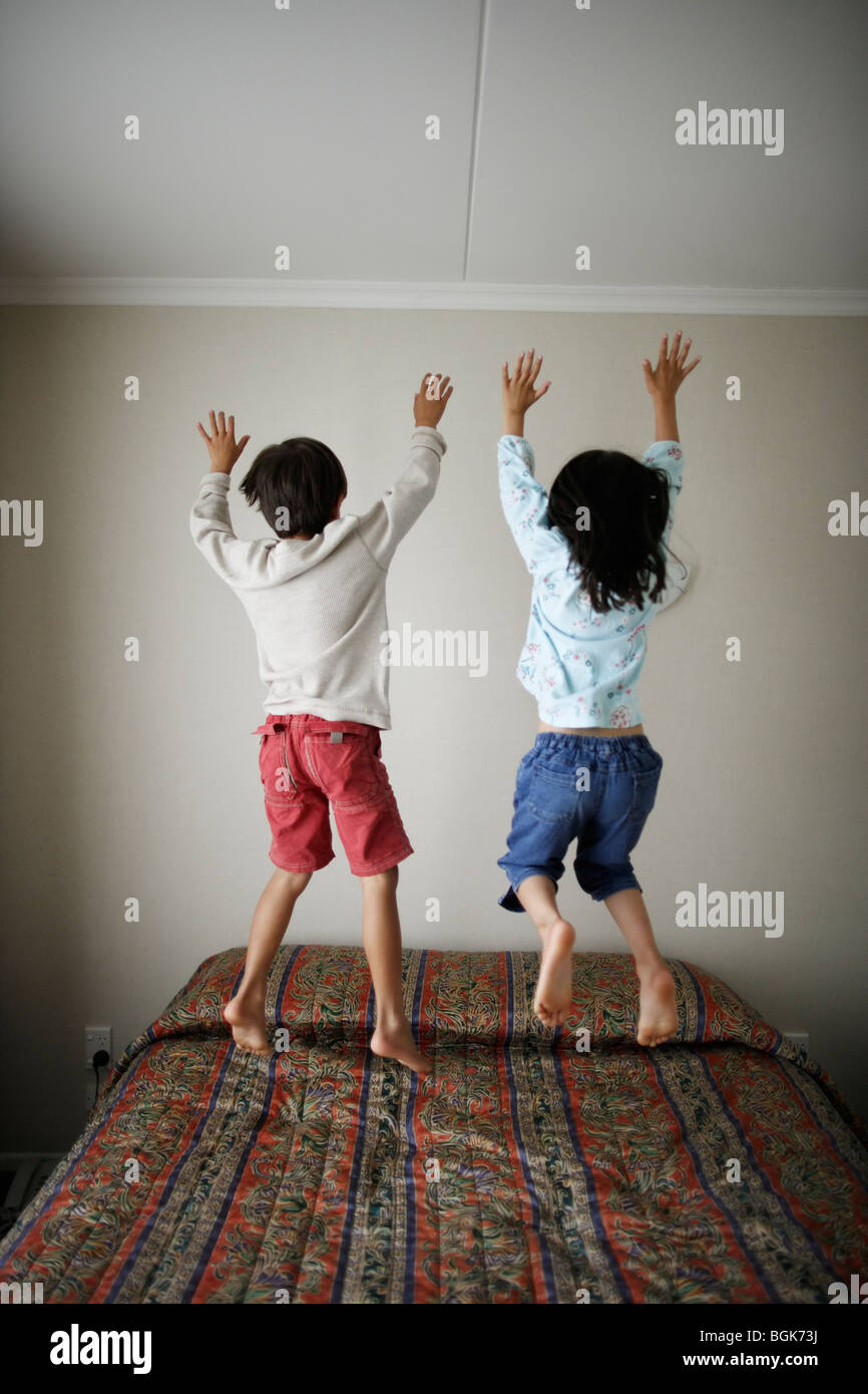 Brother and sister bounce on bed - Stock Image