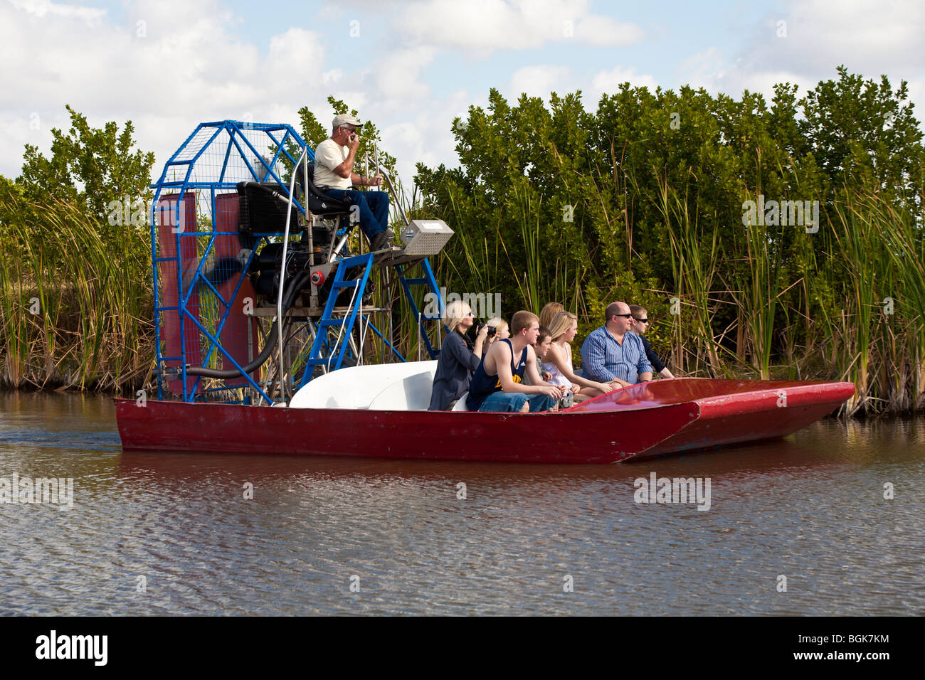 Airboat captain teaches tourists about alligators and other wildlife in mangrove swamp along Alligator Alley in - Stock Image