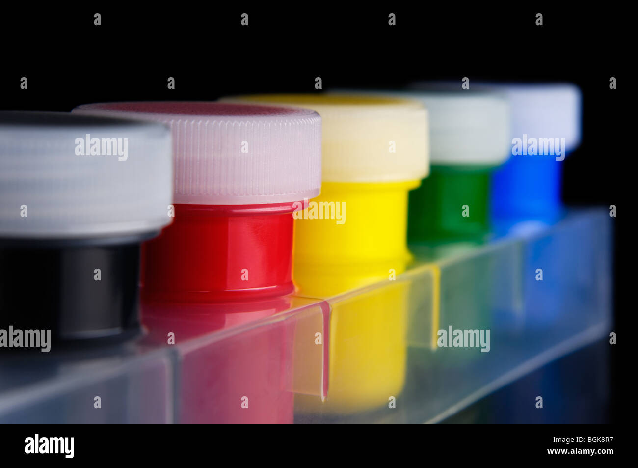 Tubes of colorful acrylic paint isolated on black background - Stock Image