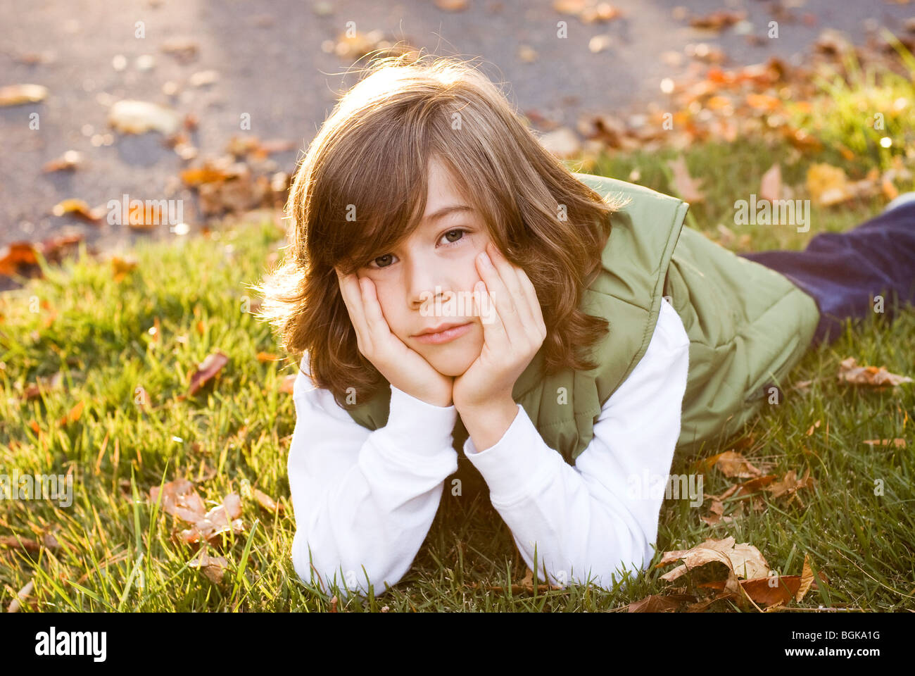boy lying in grass - Stock Image