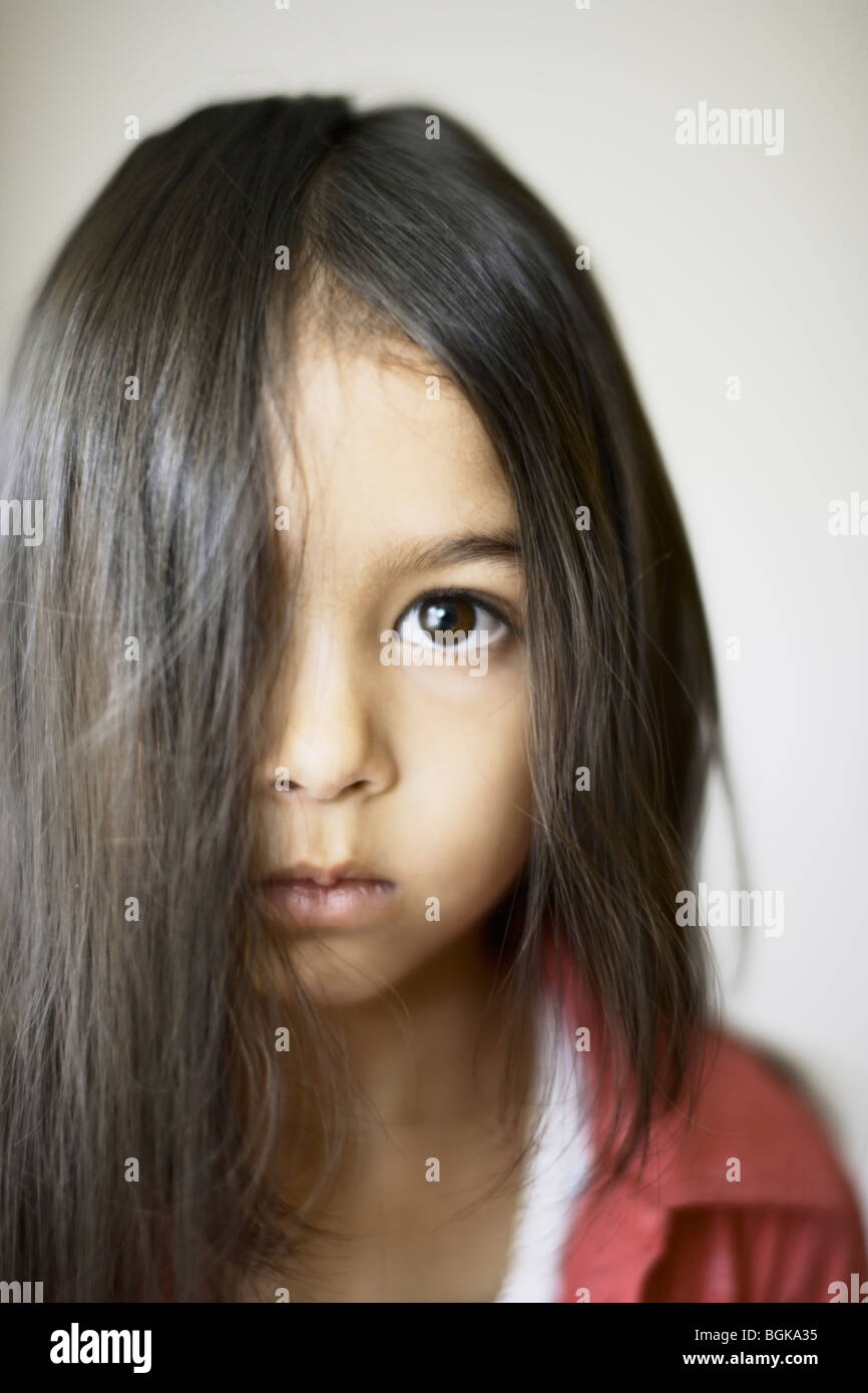 Girl six years old with hair across face - Stock Image