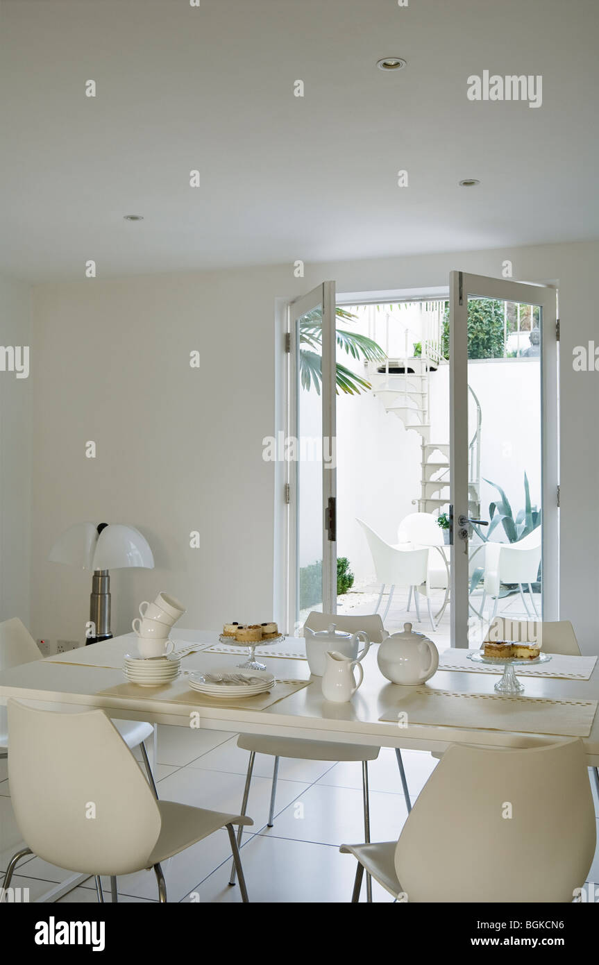 Dining area in renovated Grade II listed townhouse in Brighton with French windows and a spiral staircase. - Stock Image