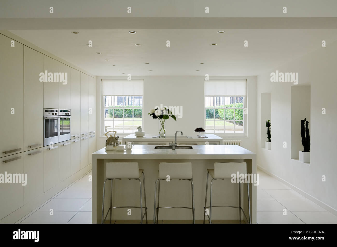 Minimalist kitchen in in white with barstools and island - Stock Image