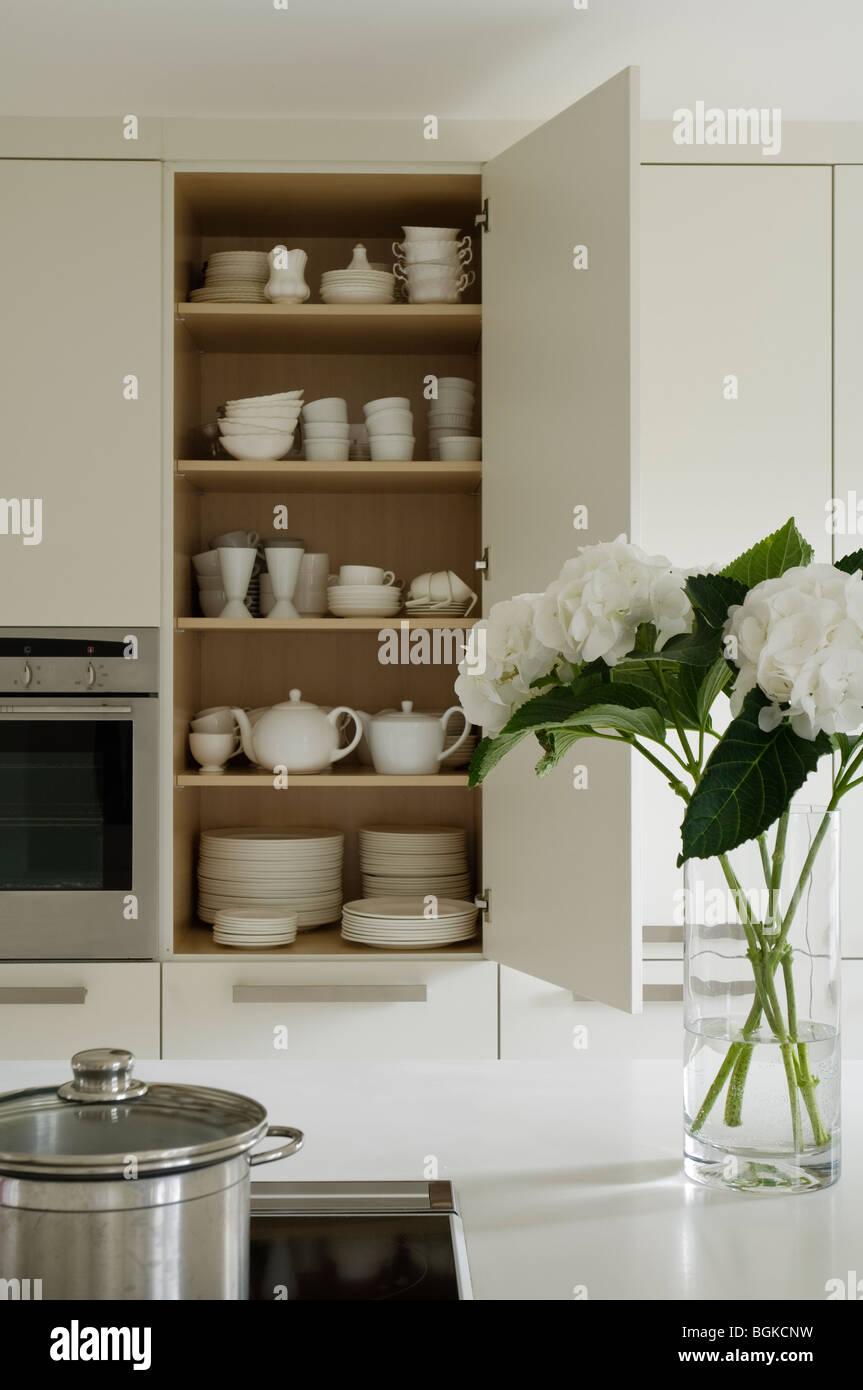 Open crockery cupboard in kitchen with hydrangea decoration Stock Photo