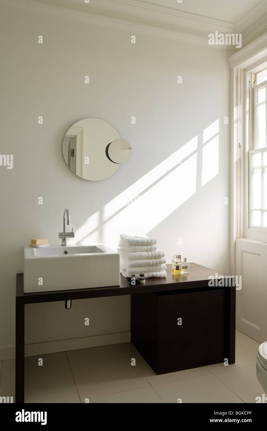 Modern bathroom with black washstand and round mirror Stock Photo ...