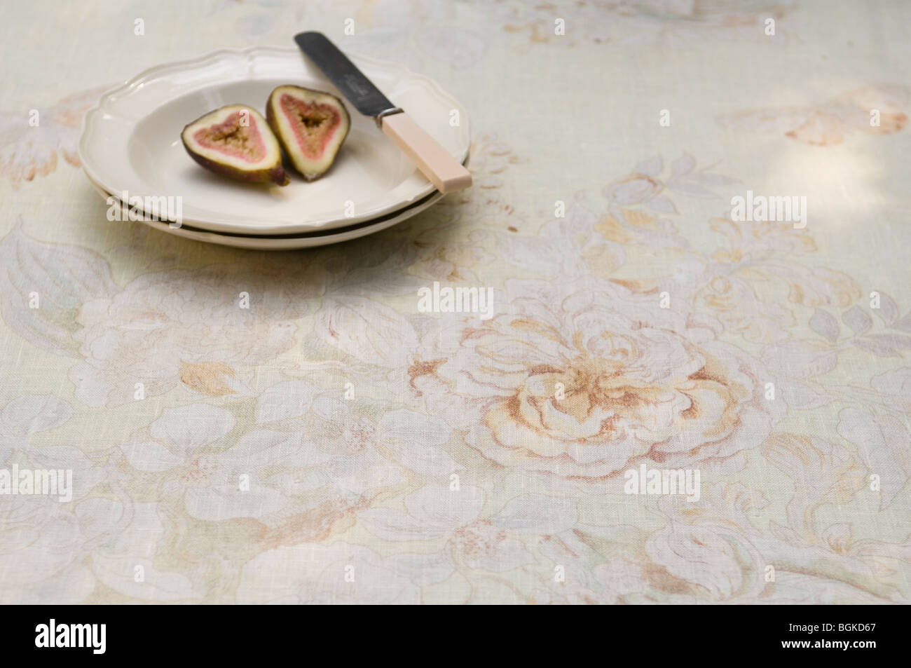 Sliced fig on plate with bone handled knife and Jim Thompson design fabric - Stock Image