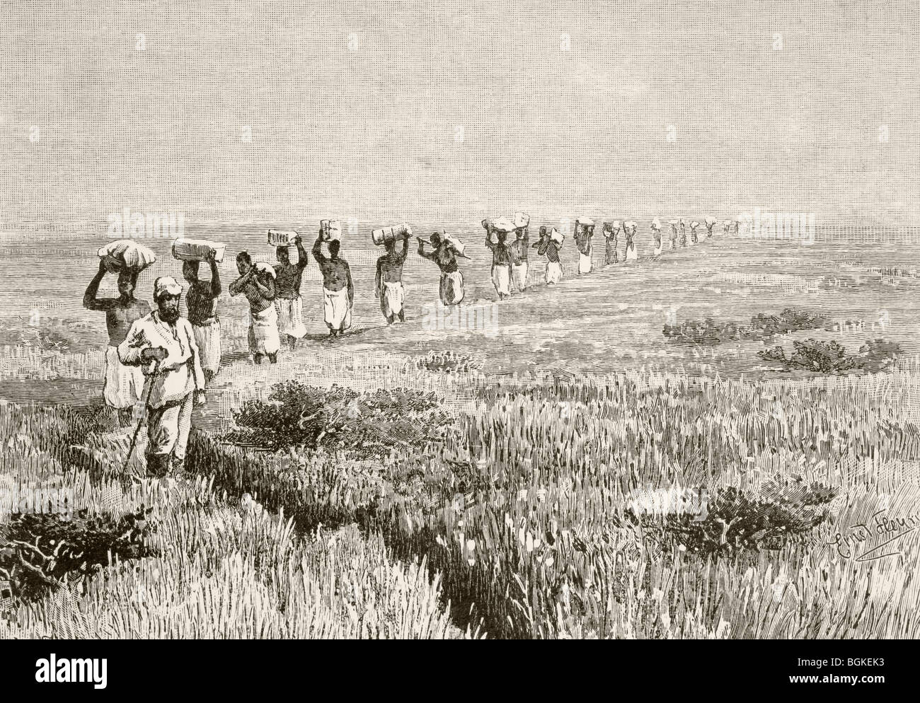 A line of porters carrying expedition supplies during a journey of exploration in East Africa in the mid 19th century. - Stock Image