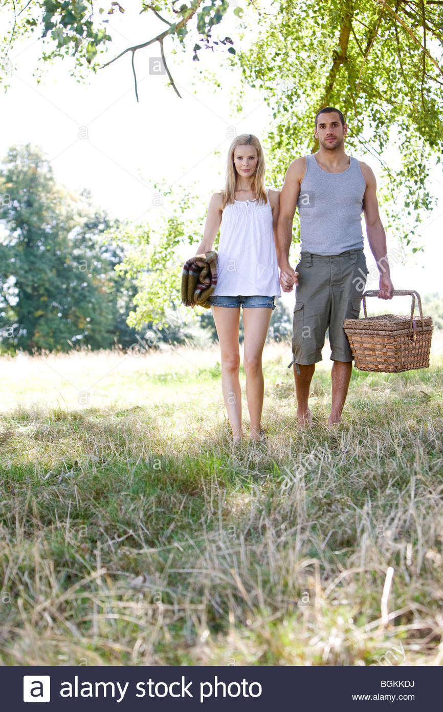 A Young Couple Holding Hands Carrying A Picnic Basket