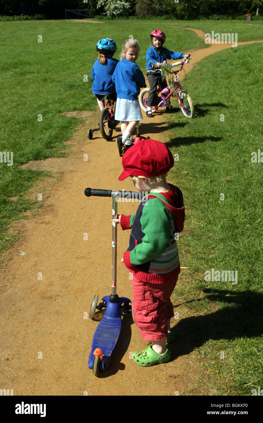 Young children cycling and scooting home from school - Stock Image