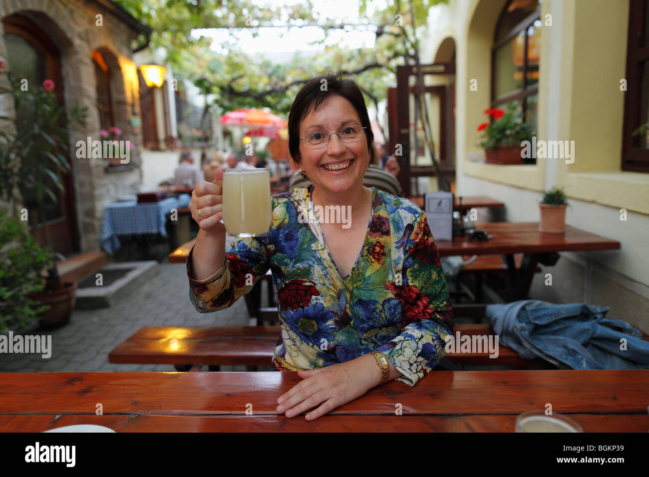 Woman with a glass of 'Sturm', 'storm', wine tavern Kicker, Rust on Lake Neusiedl, Burgenland, Austria, - Stock Image