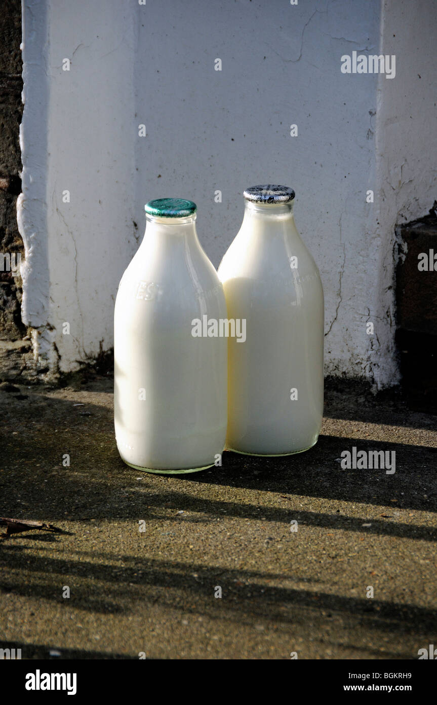 Two full milk bottles on doorstep, one green top and one silver North London England UK - Stock Image