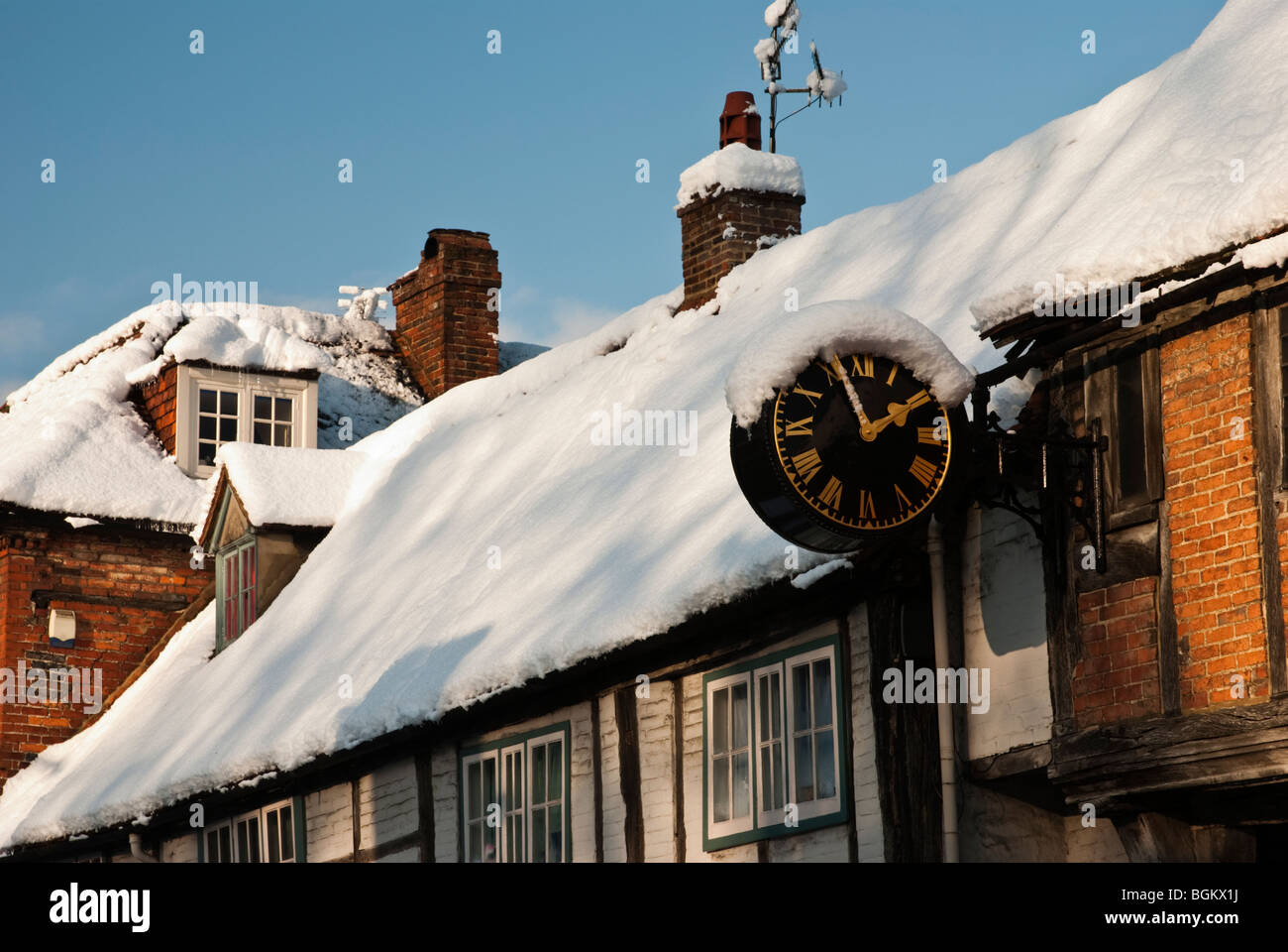 The snow covered Church Loft Clock on West Wycombe High Street. The clock dates for C1670. Buckinghamshire, England, - Stock Image
