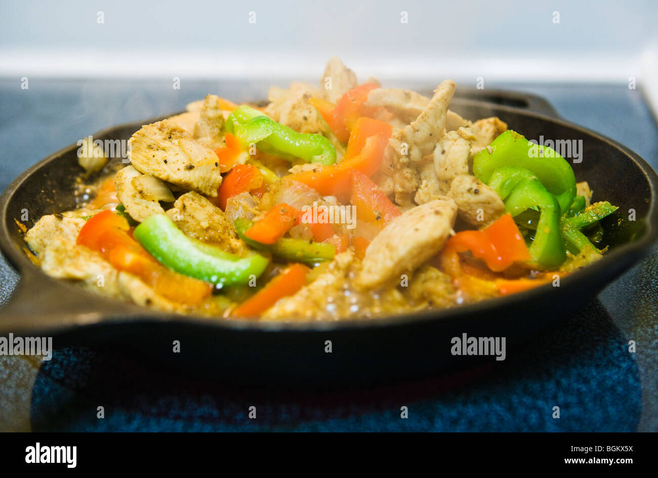 Chicken Fajitas cooking in a iron skillet on a stove top. - Stock Image