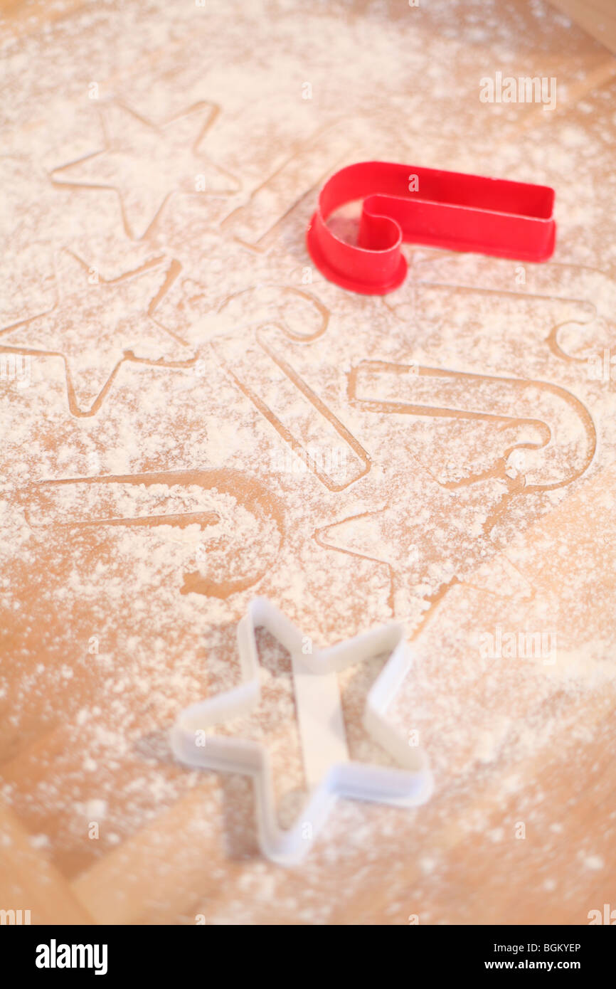 Holiday cookie cutters on flour covered surface Stock Photo