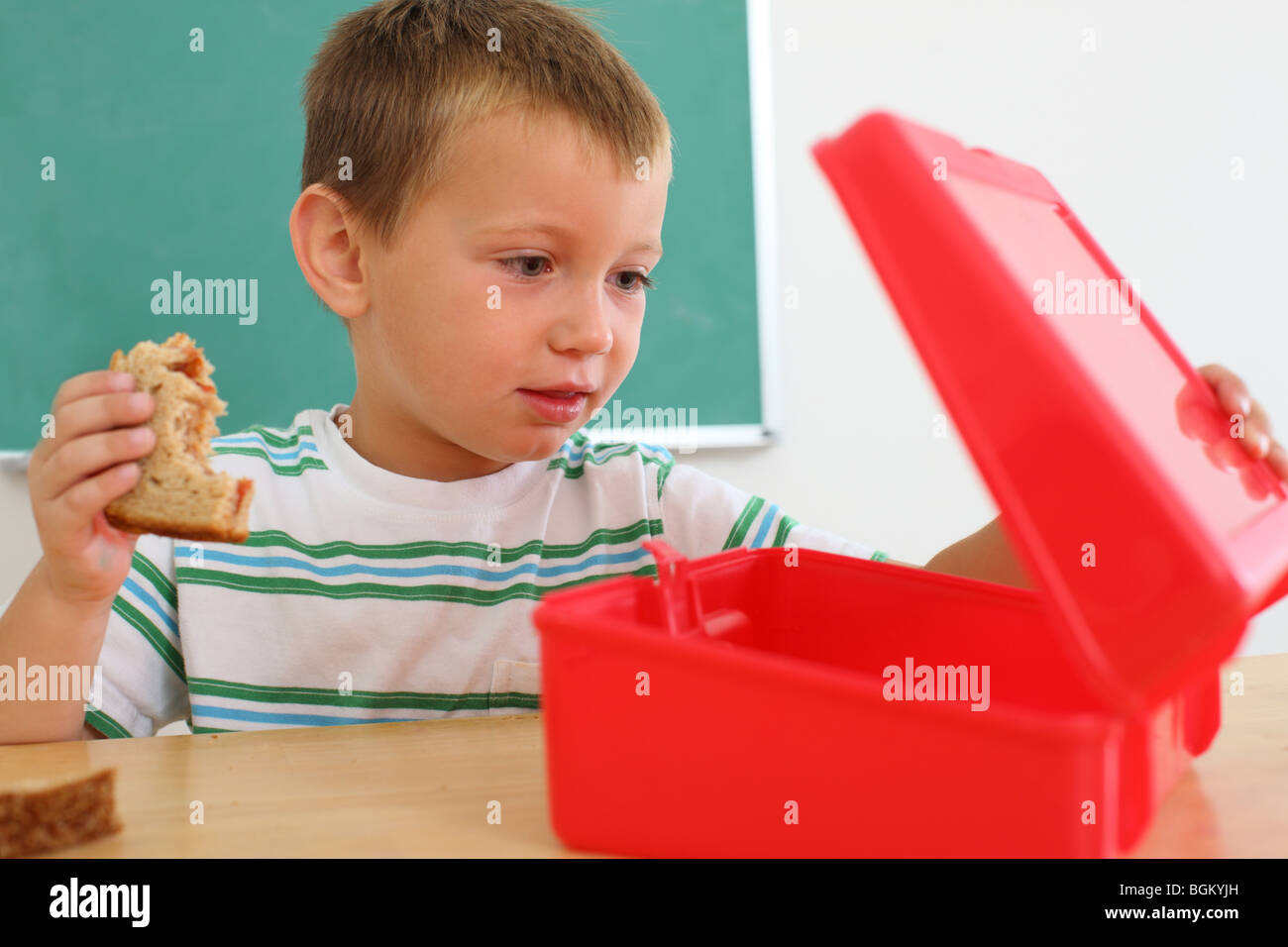 Young boy looks in lunch box - Stock Image
