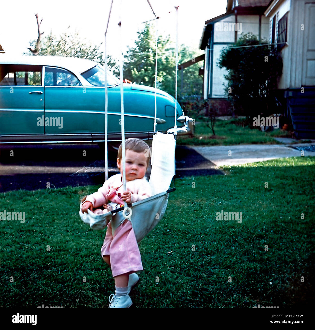 U.S.A., 1950's Family Photos, Young Girl Alone in Swing in Backyard. 'Old Family Photos' - Stock Image