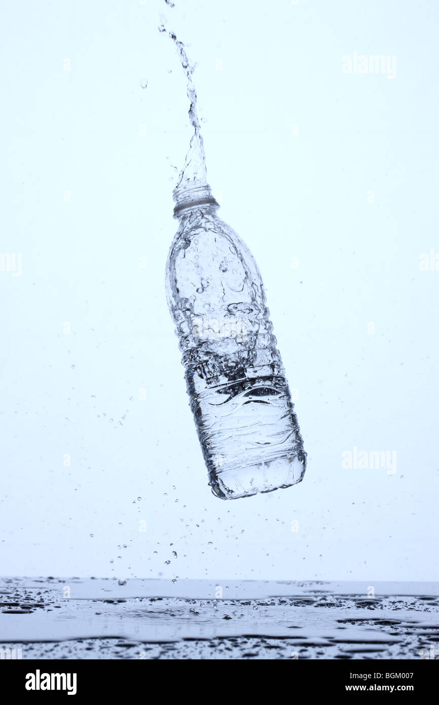 Bottle of water bouncing off surface and splashing - Stock Image