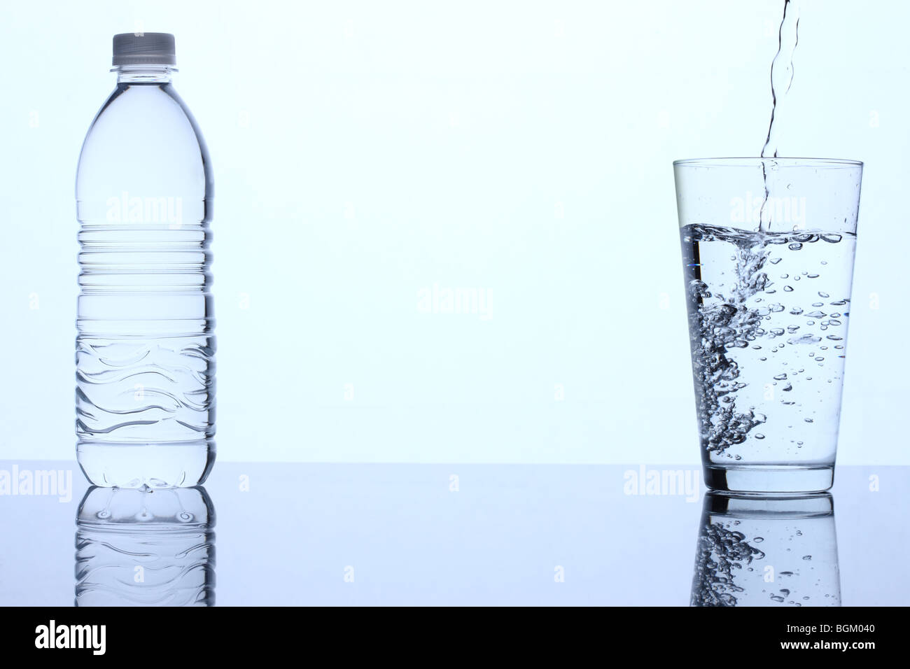 Bottle of water and glass of water being filled Stock Photo