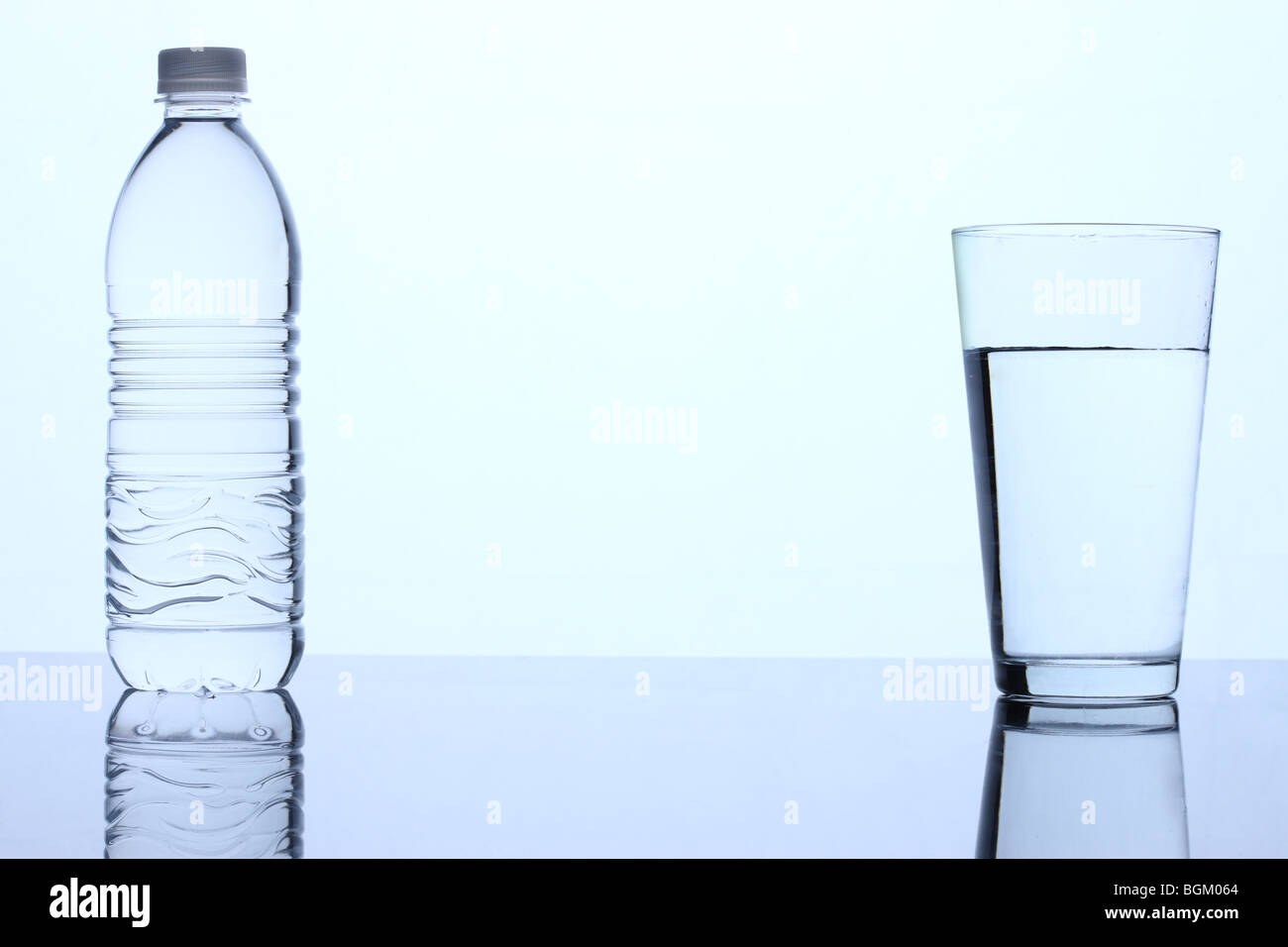 Bottle of water and glass of water - Stock Image