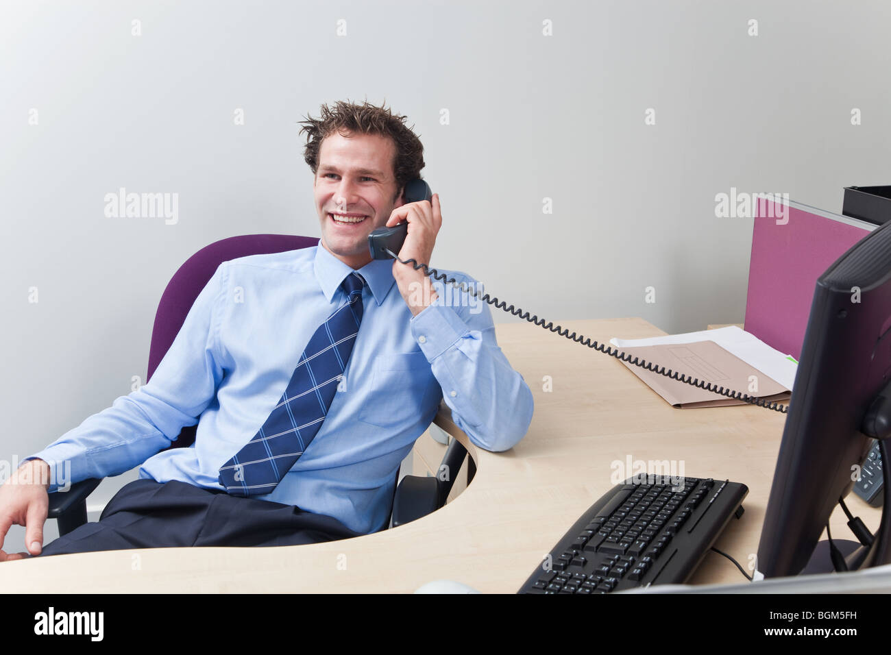 A businessman wearing shirt and tie sat at his desk chatting on the telephone. - Stock Image