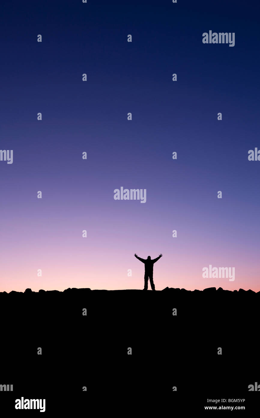 Silhouette of a man raising his hands into the sunrise after conquering a summit - Stock Image