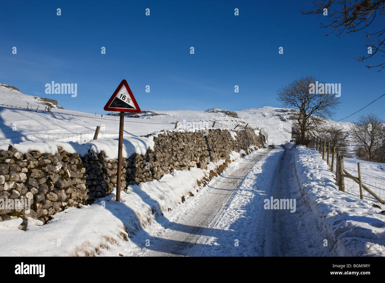 An icy, snow covered road with a 16% gradient warning sign - Stock Image